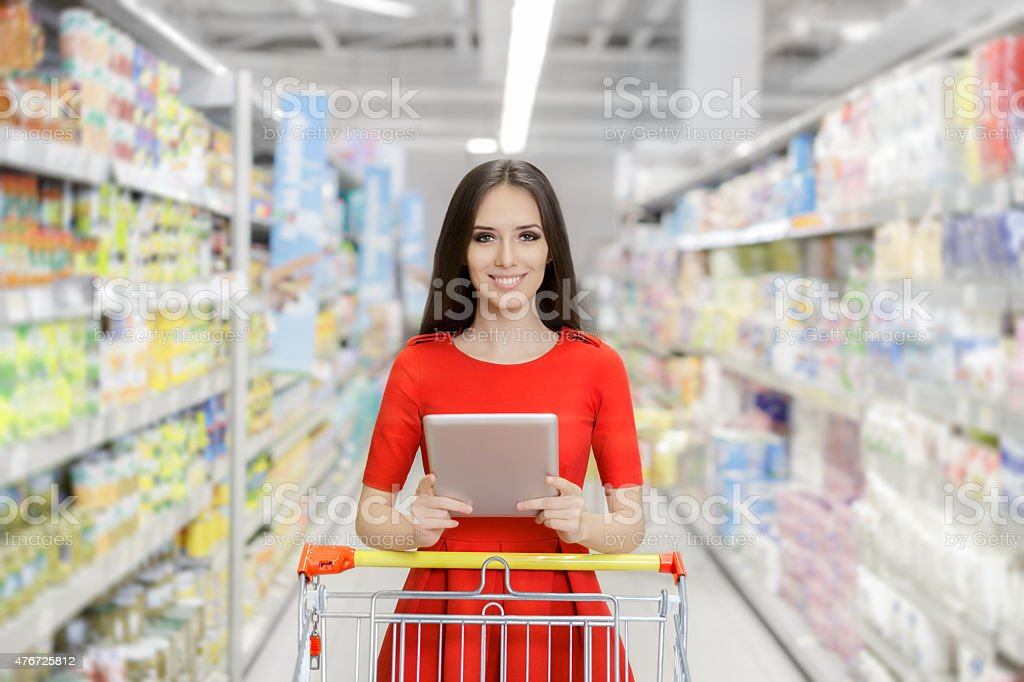 Happy Woman with Tablet Shopping  at The Supermarket stock photo