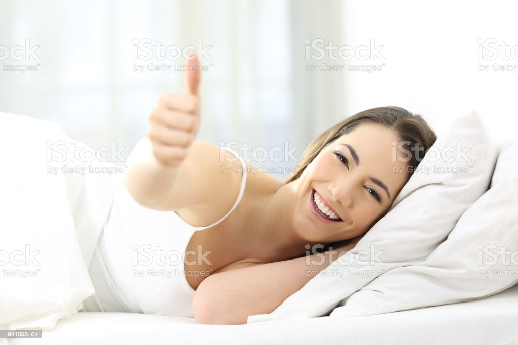 Happy woman with thumb up on the bed at home stock photo