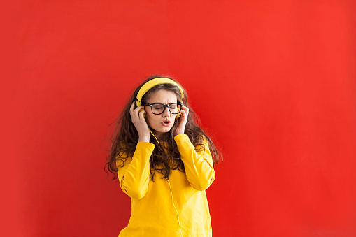 Young woman with yellow headphones and eyeglasses listening music and singing. Hands on head, eyes closed. On red background.