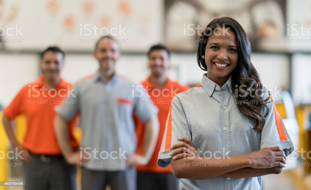 Happy woman working at a car garage stock photo