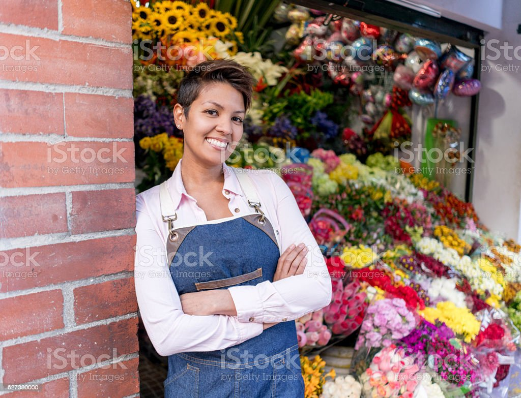 Happy woman working at a flower shop stock photo