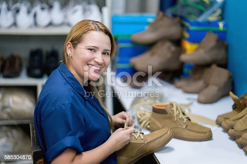 Happy woman working at a shoe-making factory in the assembly line and looking at the camera smiling