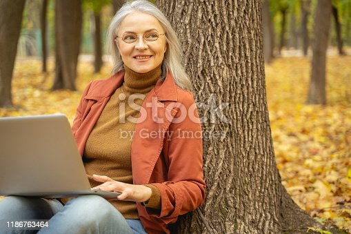 istock Happy woman working in a city park 1186763464