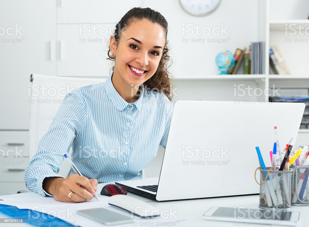 Happy woman working with paperwork and laptop stock photo