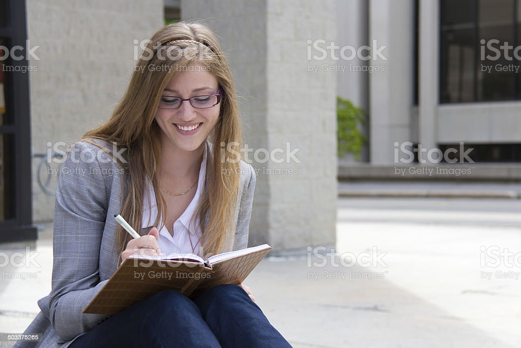 Happy woman writing in her journal stock photo