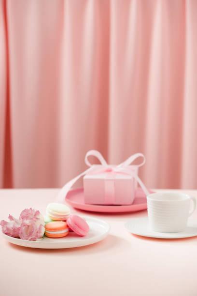 """glückliche frau/mutter """"s tag bild einer kaffee oder tee tasse und lisianthus blume mit makronen und gaben neben gardinen rosa. - tortenfiguren stock-fotos und bilder"""