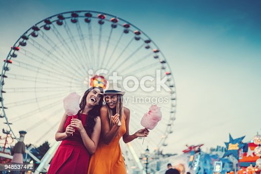 Two friends eating cotton candy and laughing at the amusement park