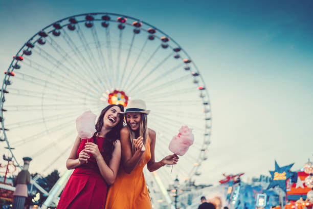 Happy women at the amusement park Two friends eating cotton candy and laughing at the amusement park ferris wheel stock pictures, royalty-free photos & images