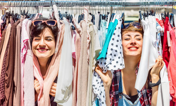 Happy women at weekly flea market - Female friends having fun together shopping cloth on sunny day - Millenial lifestyle concept with girlfriends enjoying everyday life moments - Bright vivid filter stock photo