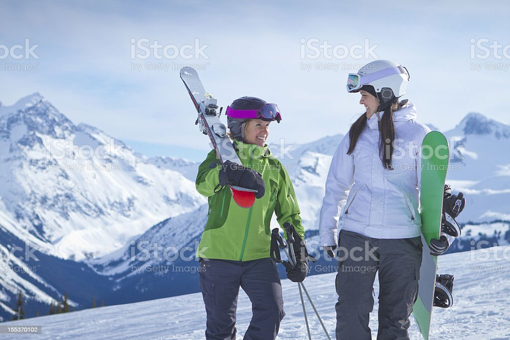 Happy women carrying ski and snowboard gear royalty-free stock photo