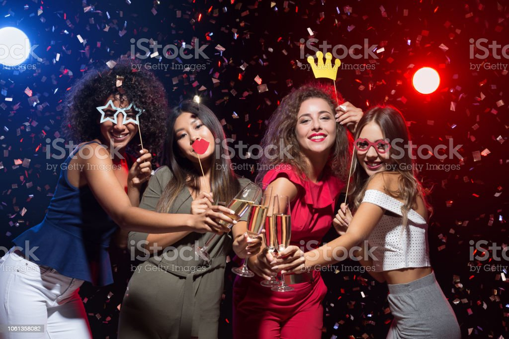Happy women celebrating New Year at nightclub stock photo