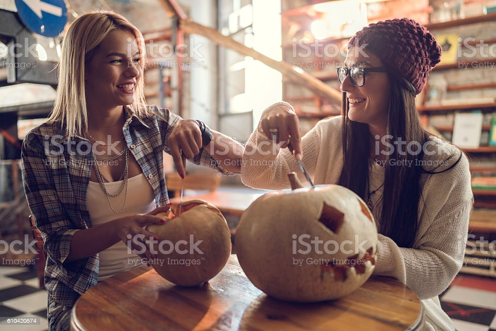 Happy women communicating while carving pumpkins for Halloween. stock photo