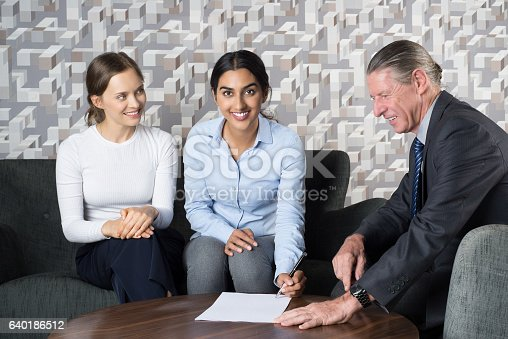 istock Happy Women Couple Signing Agreement and Agent 640186512