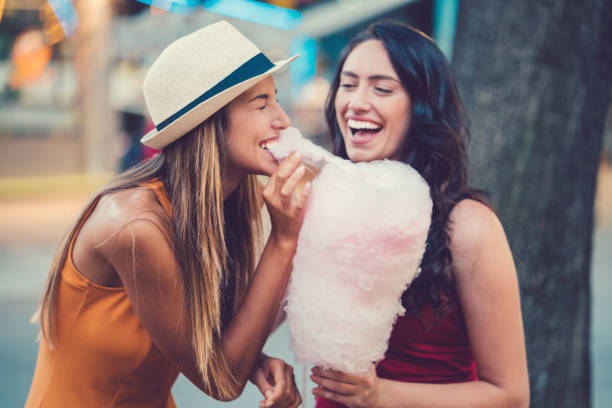 Happy women eating pink cotton candy stock photo