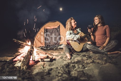 Happy female friends enjoying in camping night by the fire while drinking wine and playing a guitar.