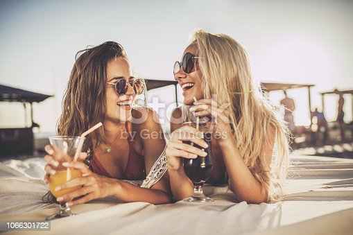 Happy female friends relaxing on a beach bed and talking while enjoying in summer cocktails.