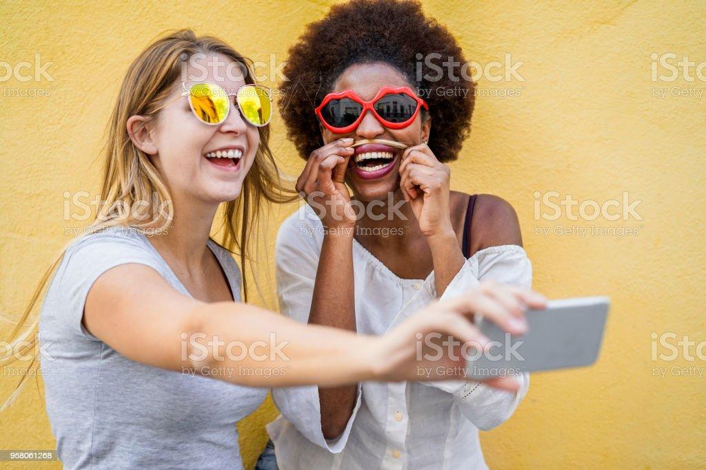 Glückliche Frauen Freunde gelbe Wand - trendige Mädchen mit Mode Sonnenbrillen Spaß gemeinsam lachen - Jugend und Freundschaft Konzept - Fokus auf afrikanischen Frauengesicht Selfie stehende Übernahme – Foto