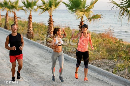 670054434istockphoto Happy women giving high-five to each other while running outdoors. 1182977668