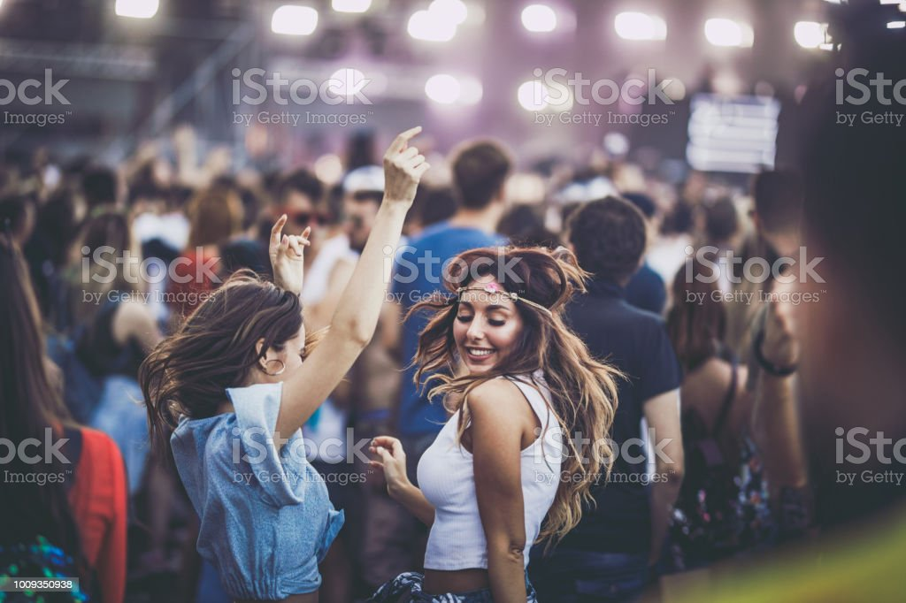 Happy women having fun while dancing on a music festival. stock photo