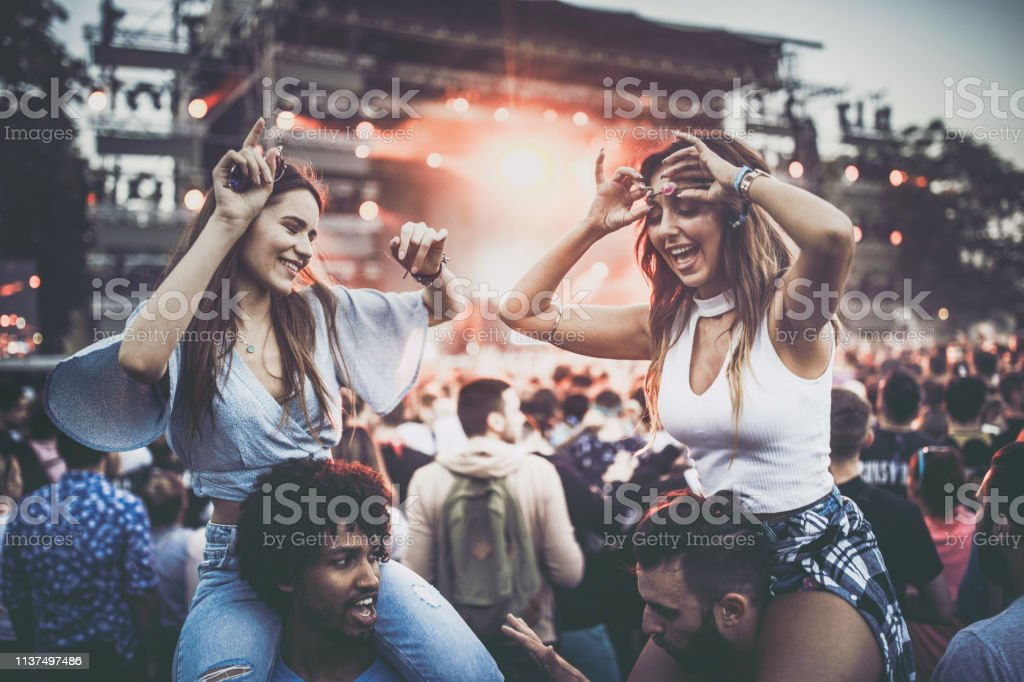 Carefree women having fun during music festival with their...