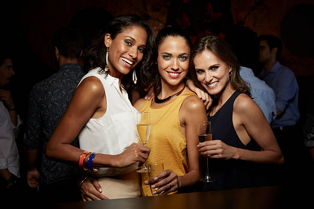 Happy women holding champagne flutes in nightclub stock photo