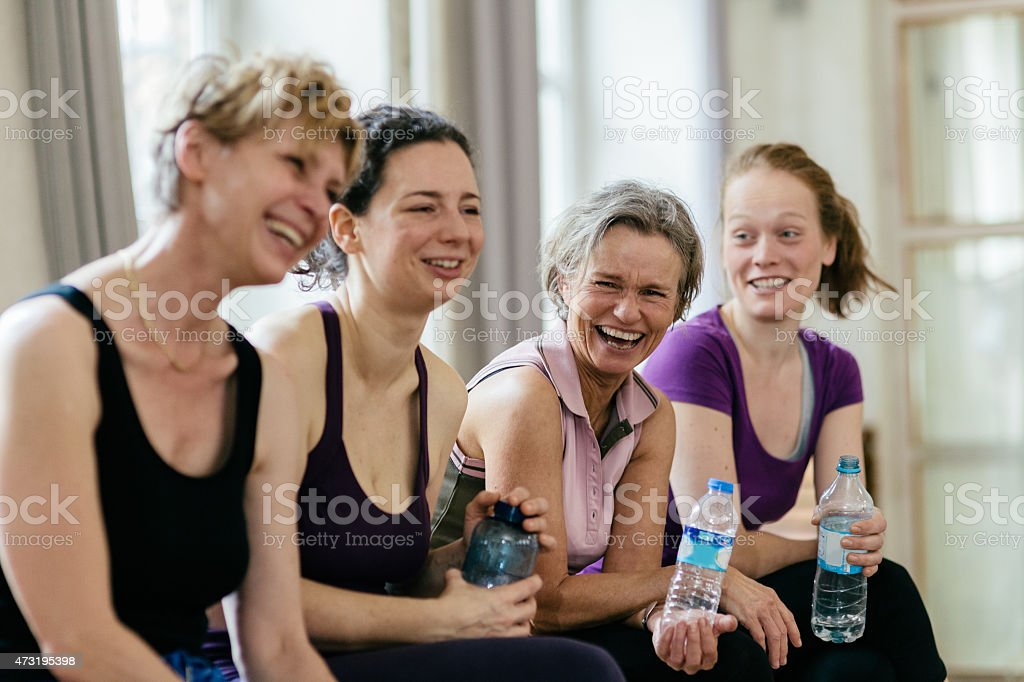 Happy women holding water bottles in gym stock photo