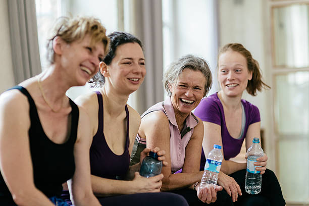 happy women holding water bottles in gym - gym skratt bildbanksfoton och bilder