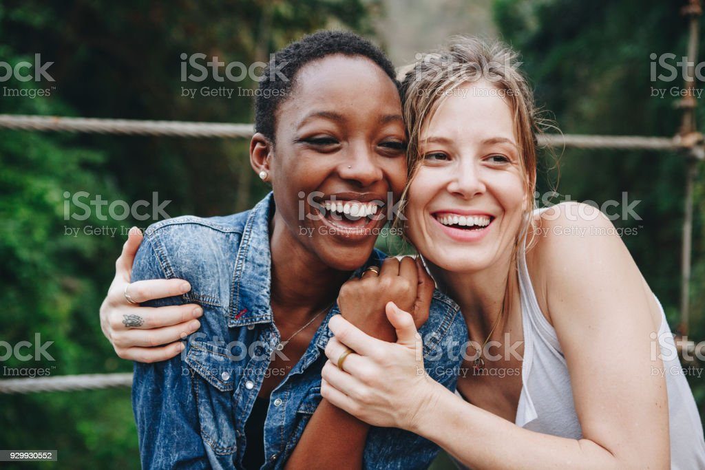 Happy women hugging each other stock photo