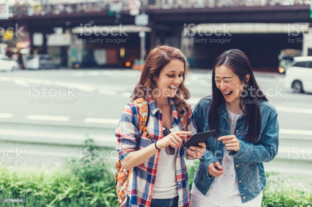 Happy women in Tokyo using tablet at the street royalty-free stock photo