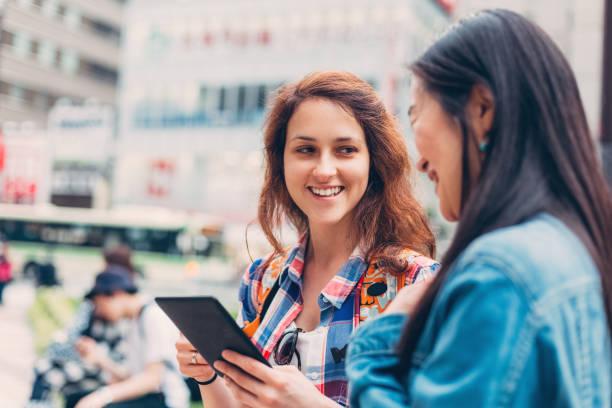 通りでタブレットを使用して東京で幸せな女性 ストックフォト