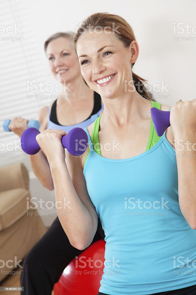 Happy women lifting weights exercising royalty-free stock photo