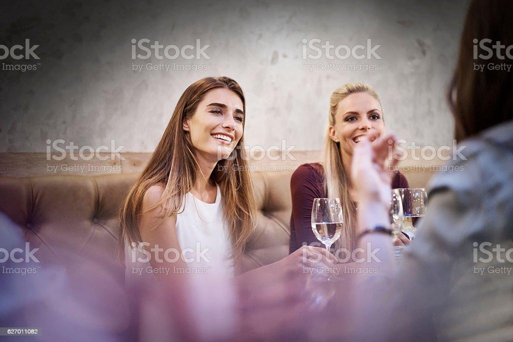 Happy women listening to friend in restaurant - Photo