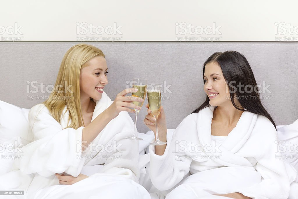 happy women or girlfriends clinking champagne glasses in bed stock photo