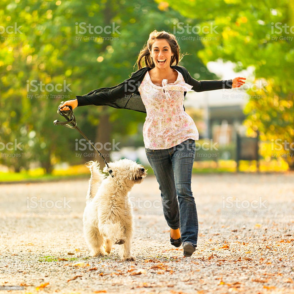 Happy women running with her dog in the park stock photo