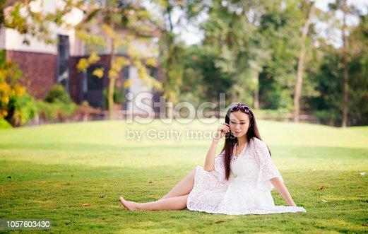 istock Happy women sit on the lawn 1057603430