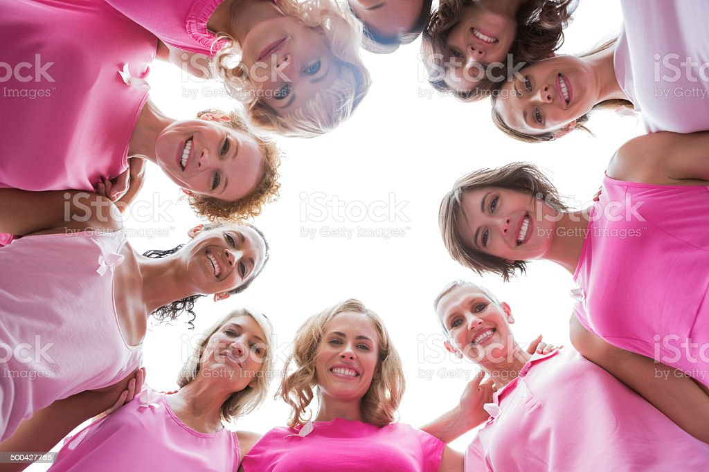 Happy women smiling in circle wearing pink for breast cancer stock photo