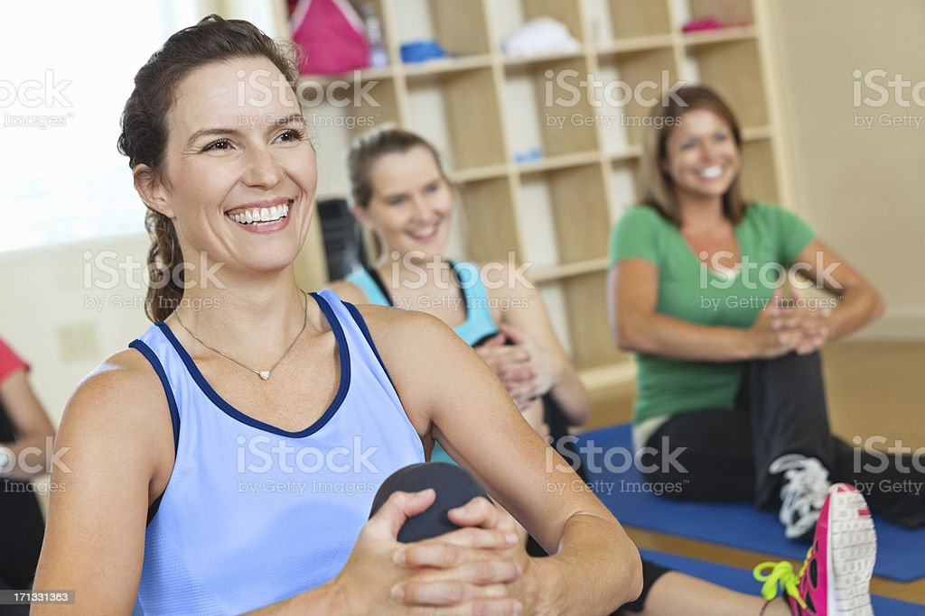 Happy women stretching on the floor in their exercise class royalty-free stock photo