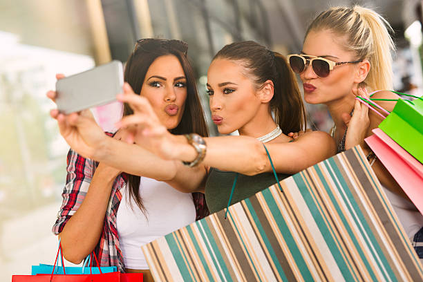 Happy women taking a selfie while resting from shopping. Happy women taking a selfie while resting from shopping. puckering stock pictures, royalty-free photos & images