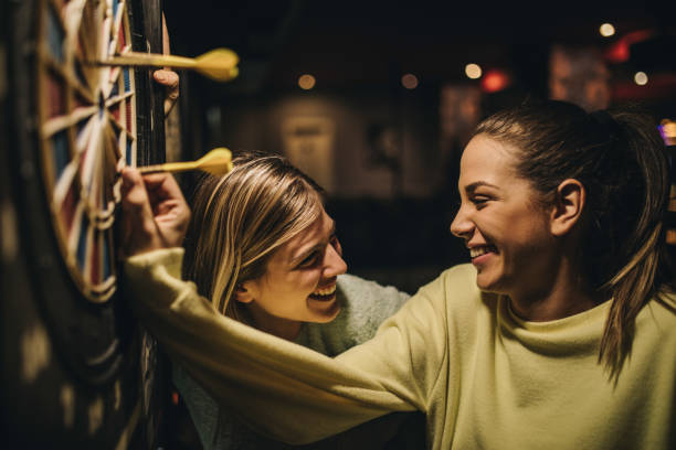 Happy women talking while removing darts from dartboard. stock photo