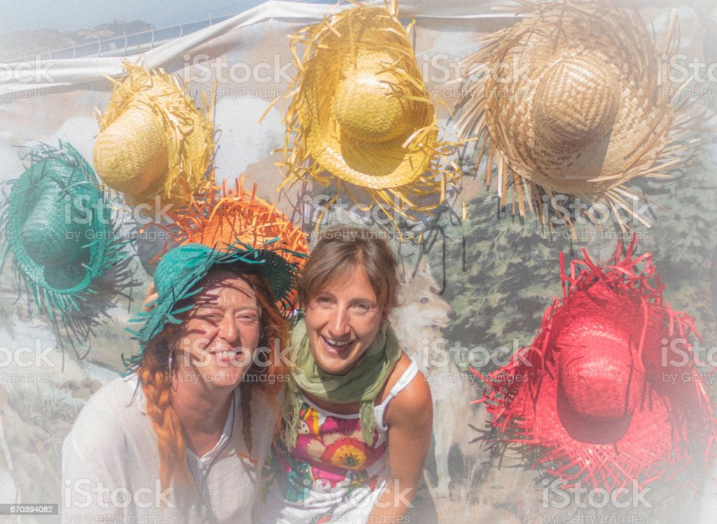 Happy Women Trying On Hats stock photo