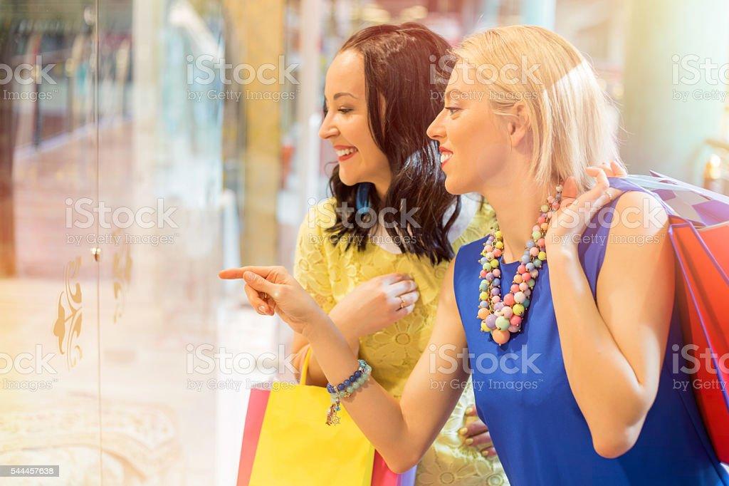 Happy women window- shopping at the mall stock photo