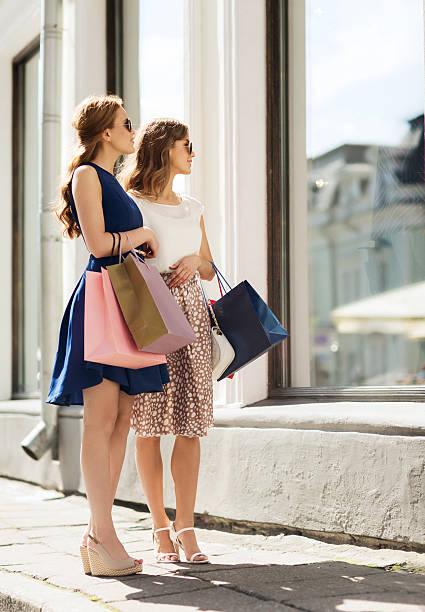 glückliche frauen mit einkaufstaschen im schaufenster - sommer teenagermode stock-fotos und bilder