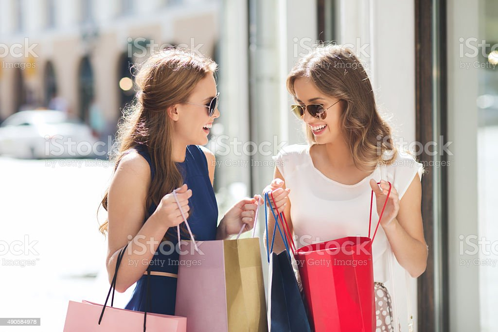 happy women with shopping bags in city royalty-free stock photo