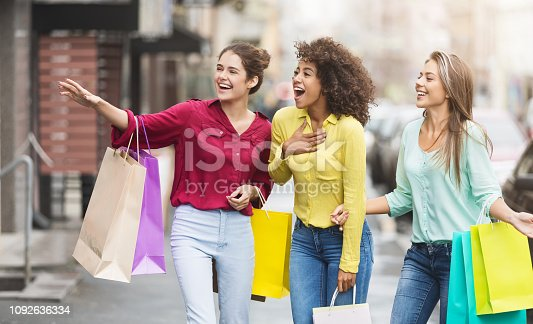 Happy women with shopping bags, looking at shop windows, walking along city street