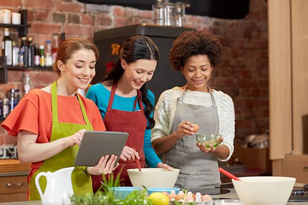 Glückliche Frau mit tablet pc zu kochen in der Küche – Foto