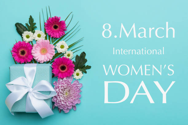 Happy Women's Day Pastel Candy Colors Background. Floral flat lay greeting card with beautifully wrapped present. stock photo
