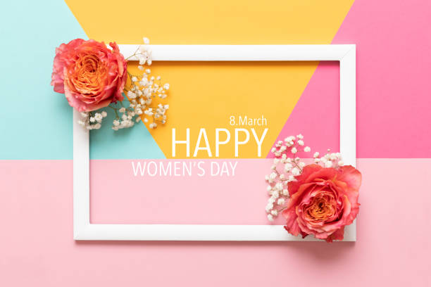 Happy Women's Day Pastel Colored Background. Flat lay greeting card with beautiful coral hue roses. stock photo