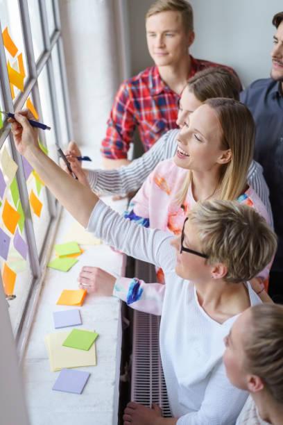 glückliche arbeitskollegen tauschen ideen im büro aus - mitarbeiterengagement stock-fotos und bilder