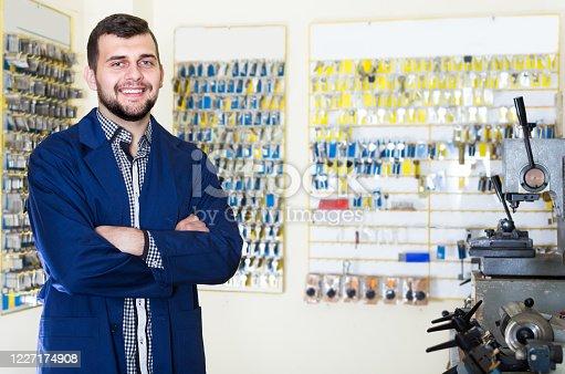 Happy male worker demonstrating his tools for making keys in workshop