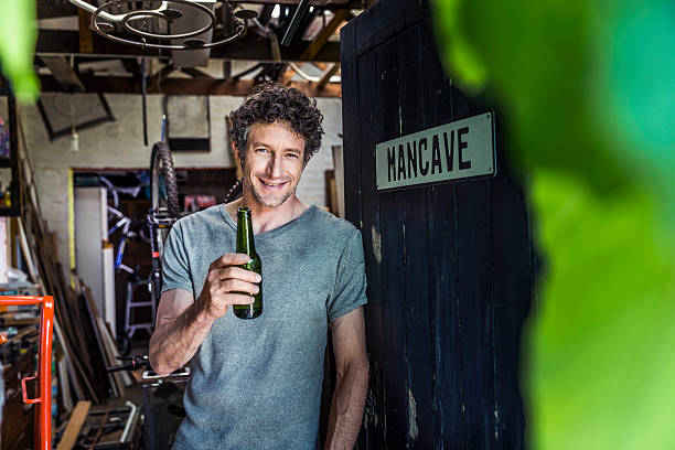Happy worker holding beer bottle in workshop A photo of happy worker holding beer bottle at doorway. Portrait of craftsperson is in casuals. Confident repairman is in his workshop. man cave stock pictures, royalty-free photos & images